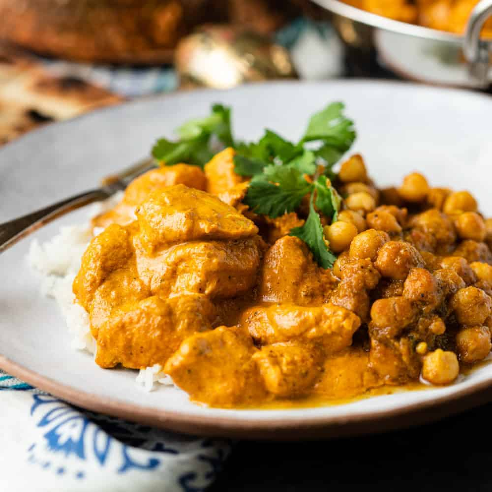 butter chicken with chickpea masala on white plate