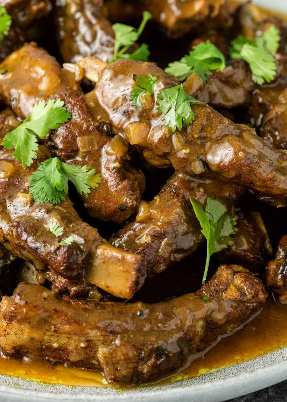 close up photo: pork ribs in Instant Pot covered with brown sauce and cilantro garnish