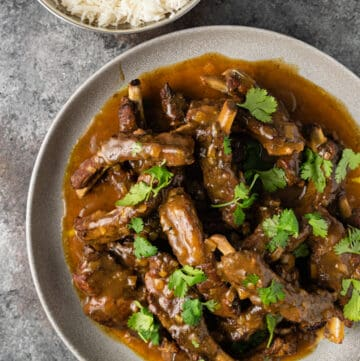 overhead photo: curried pork ribs covered in rich curry sauce on white dinner plate