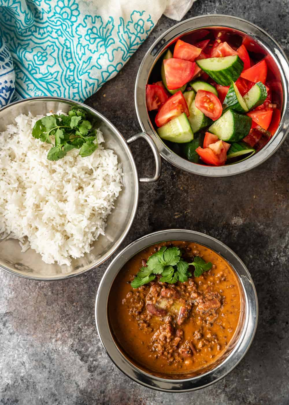 serving bowls of black dal, rice and cucumbers with tomatoes
