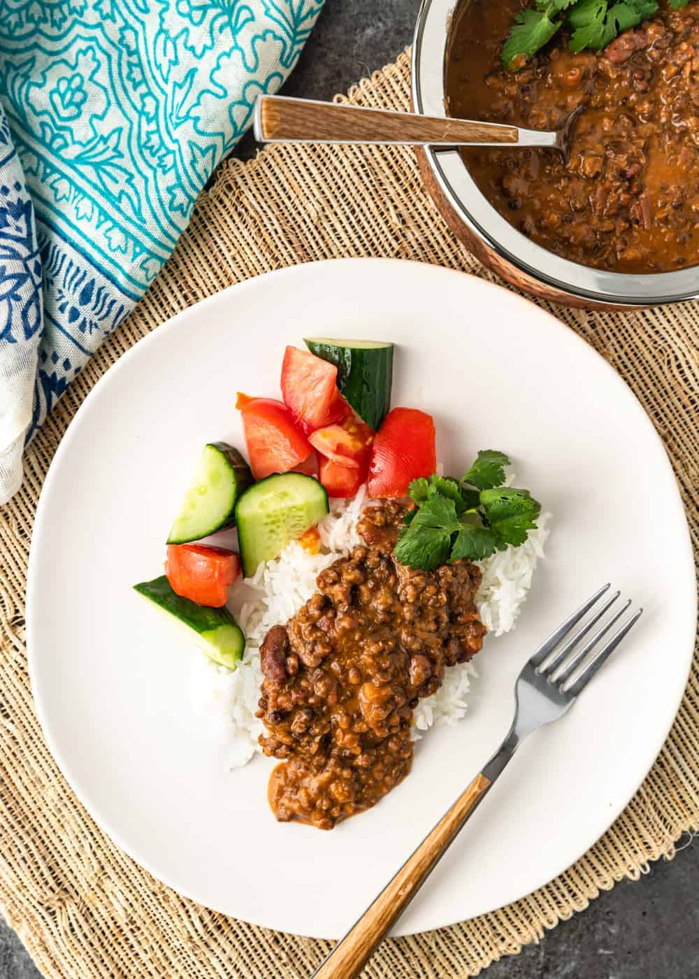 black dal makhani served over rice with vegetables on white plate