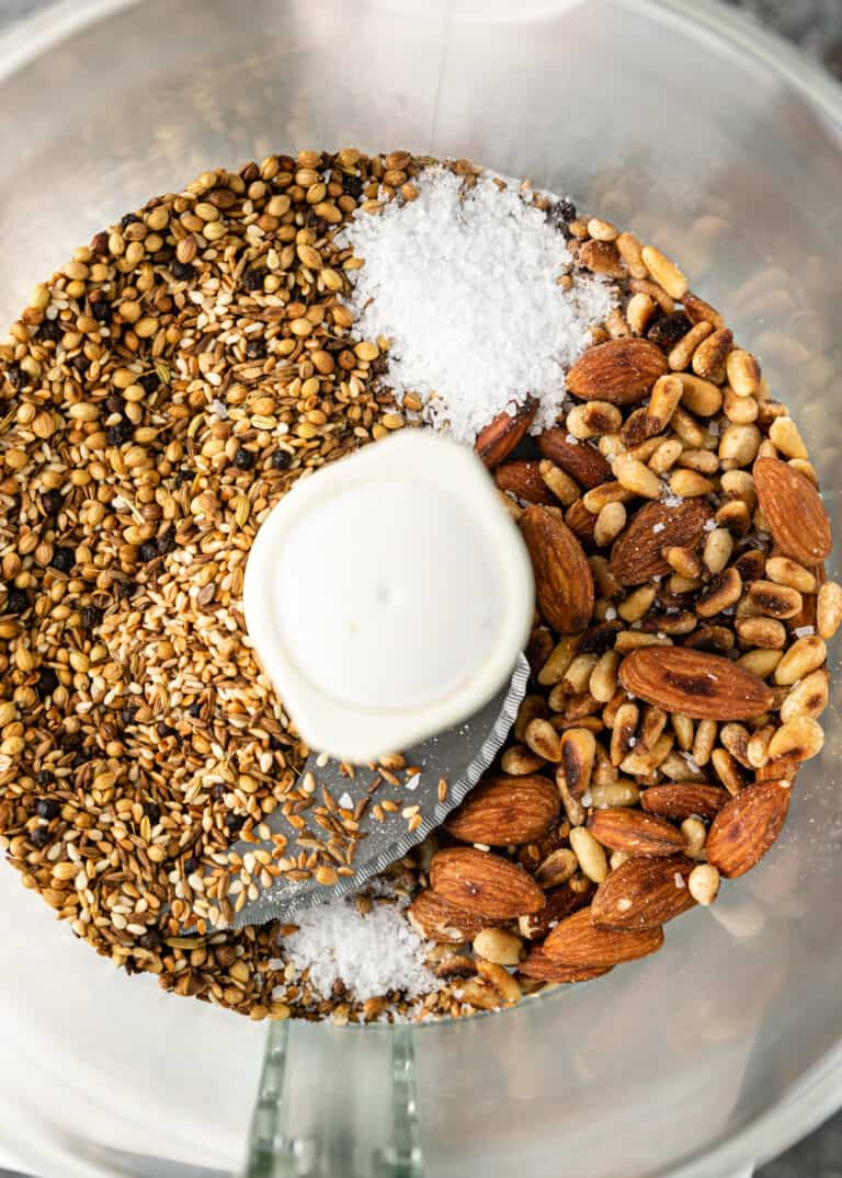 overhead image: nuts, seeds, and spices in bowl of a food processor to make a dukkah recipe