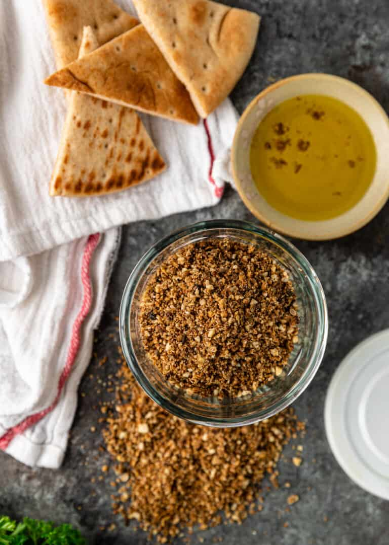 overhead image: bowl of homemade spice blend made from toasted almonds, seeds, and spices next to pita bread and dipping sauce
