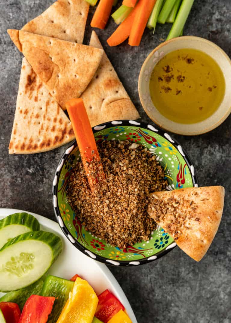 overhead image: Egyptian dukkah in green pottery bowl with carrot stick and slice of pita bread