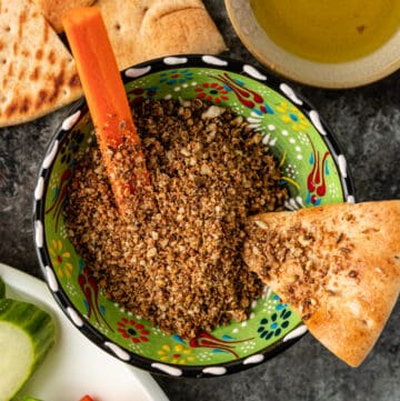 overhead image: Egyptian dukkah in green pottery bowl with slice of pita bread