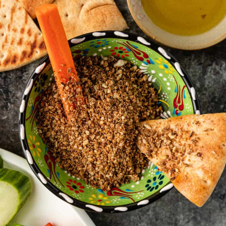 overhead image: Egyptian dukkah in a green pottery bowl with slice of pita bread