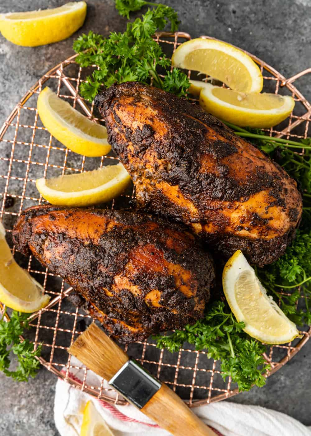 overhead- plate of iraqi grilled chicken quarters with lemon wedges and fresh parsley