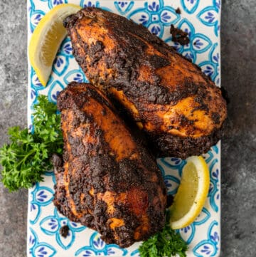 two roasted chicken breasts on blue patterned plate