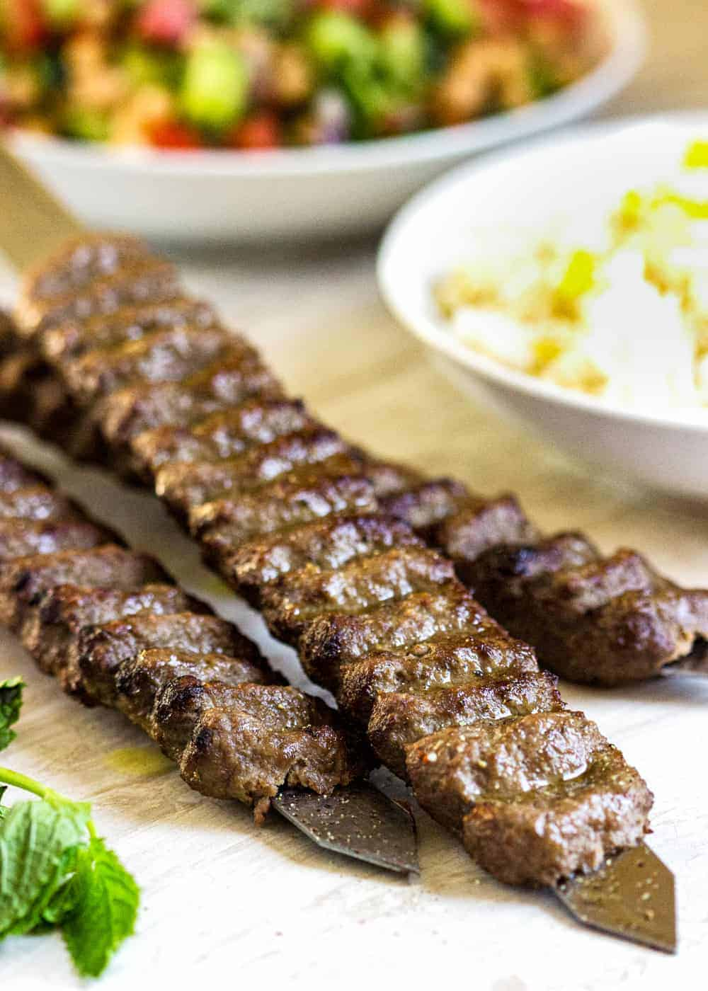 beef and lamb kabobs on a table with bowls of side dishes