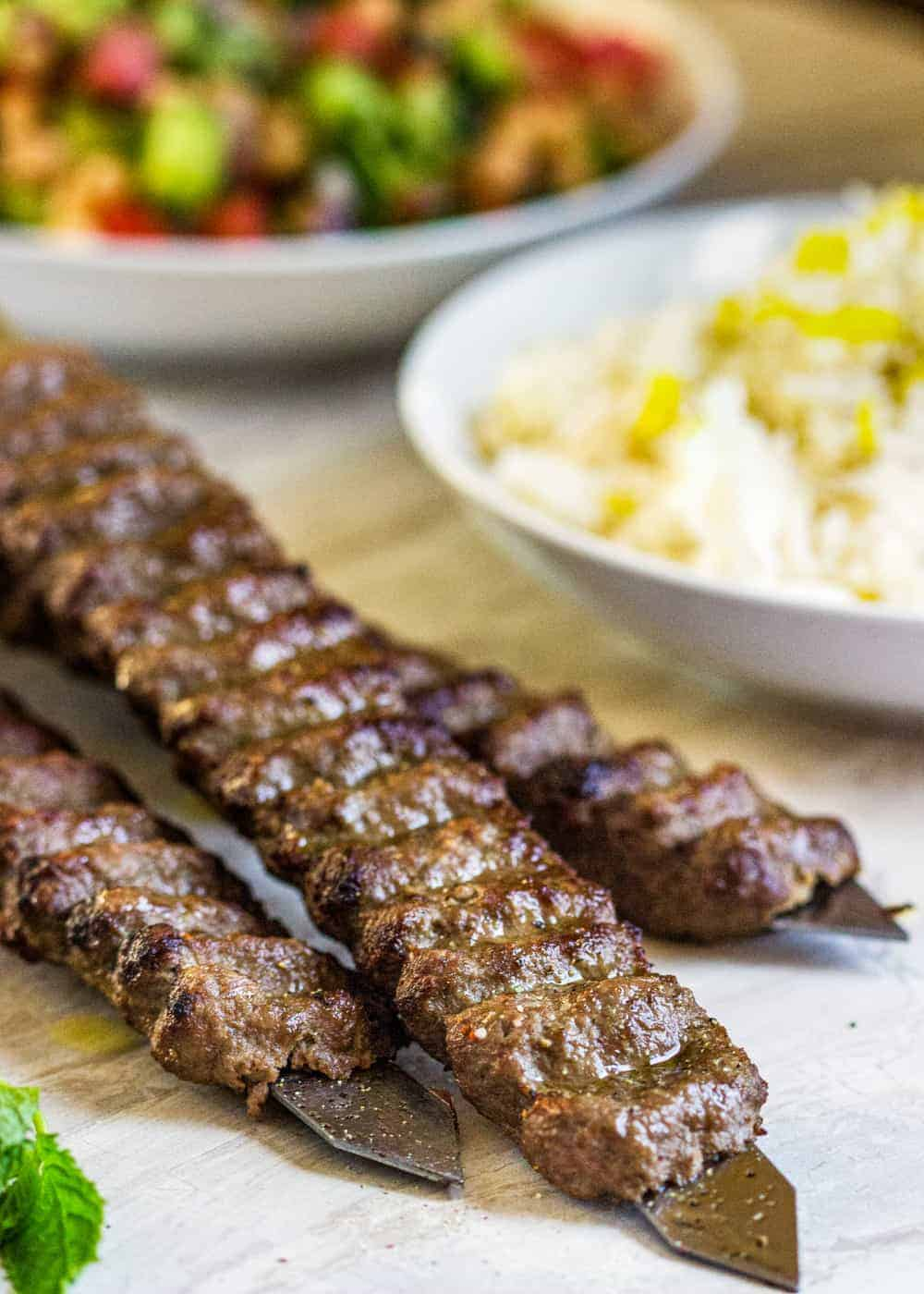Koobideh kabobs in the foreground and bowls of rice and salad in the background