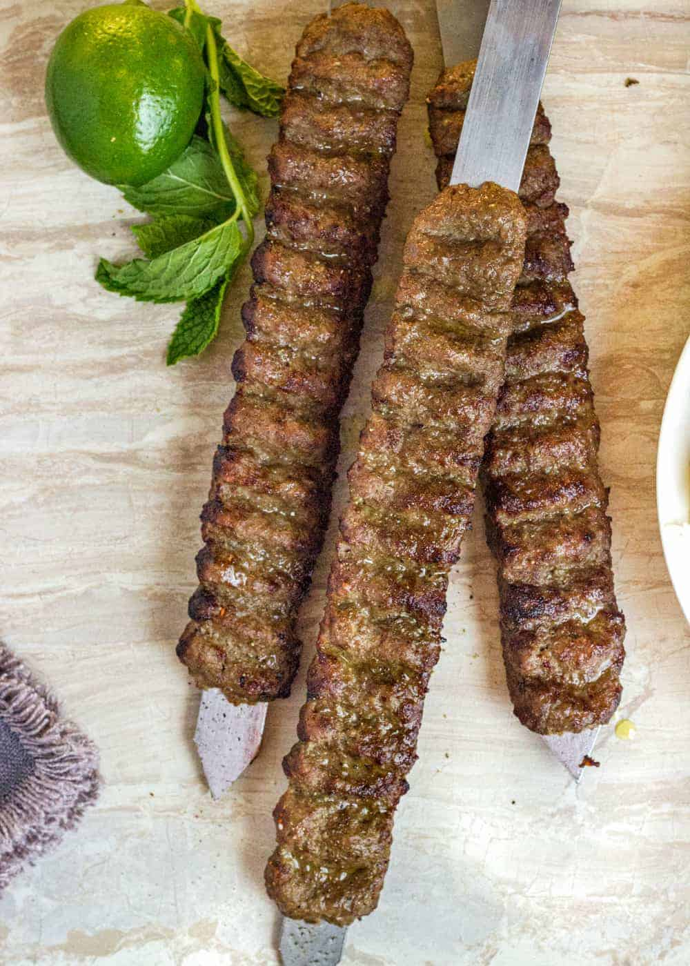 meat kabobs on flat skewers next to fresh mint leaves and a whole lime