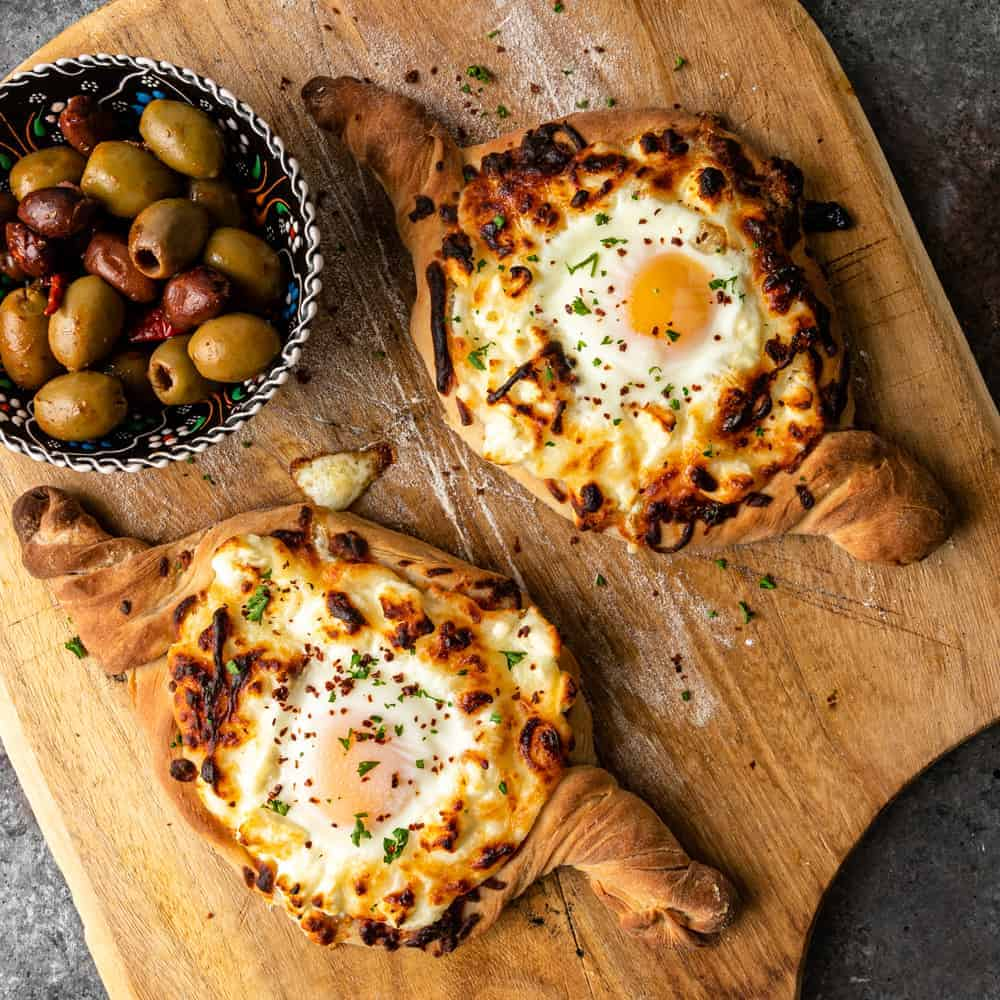 2 loaves of Georgian cheese bread and a bowl of olives on a wood serving board