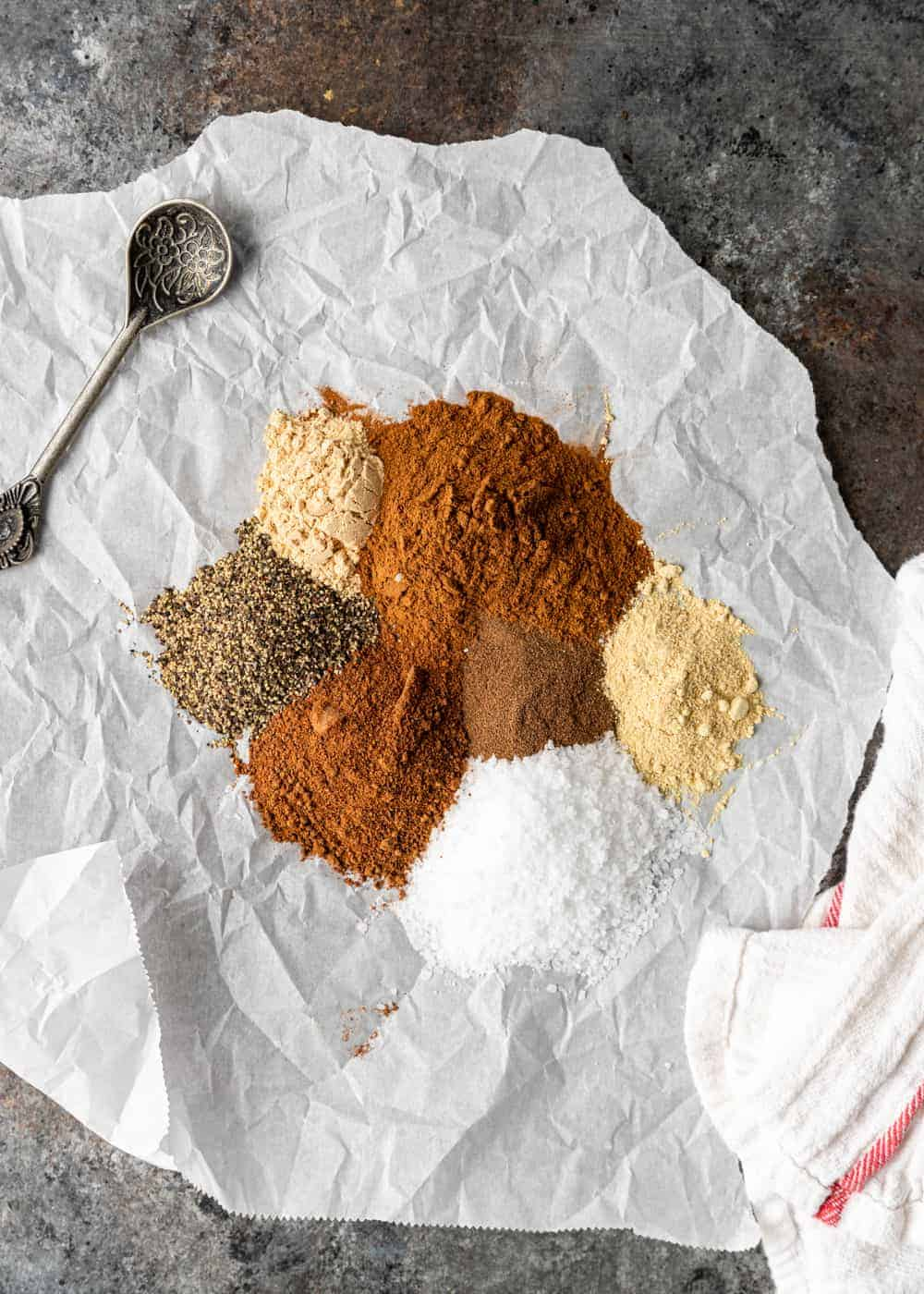 overhead: seven spices and antique spice spoon on crumpled sheet of parchment paper