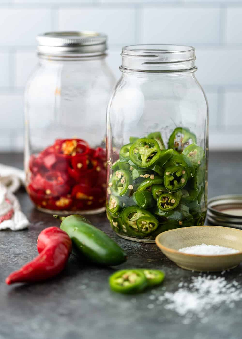 2 large glass mason jars on counter top - one with sliced red jalapenos and the other with green jalapenos