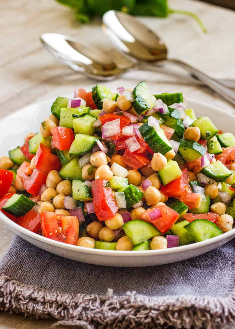 chopped vegetable and chickpea salad in a white bowl with metal spoons in the background
