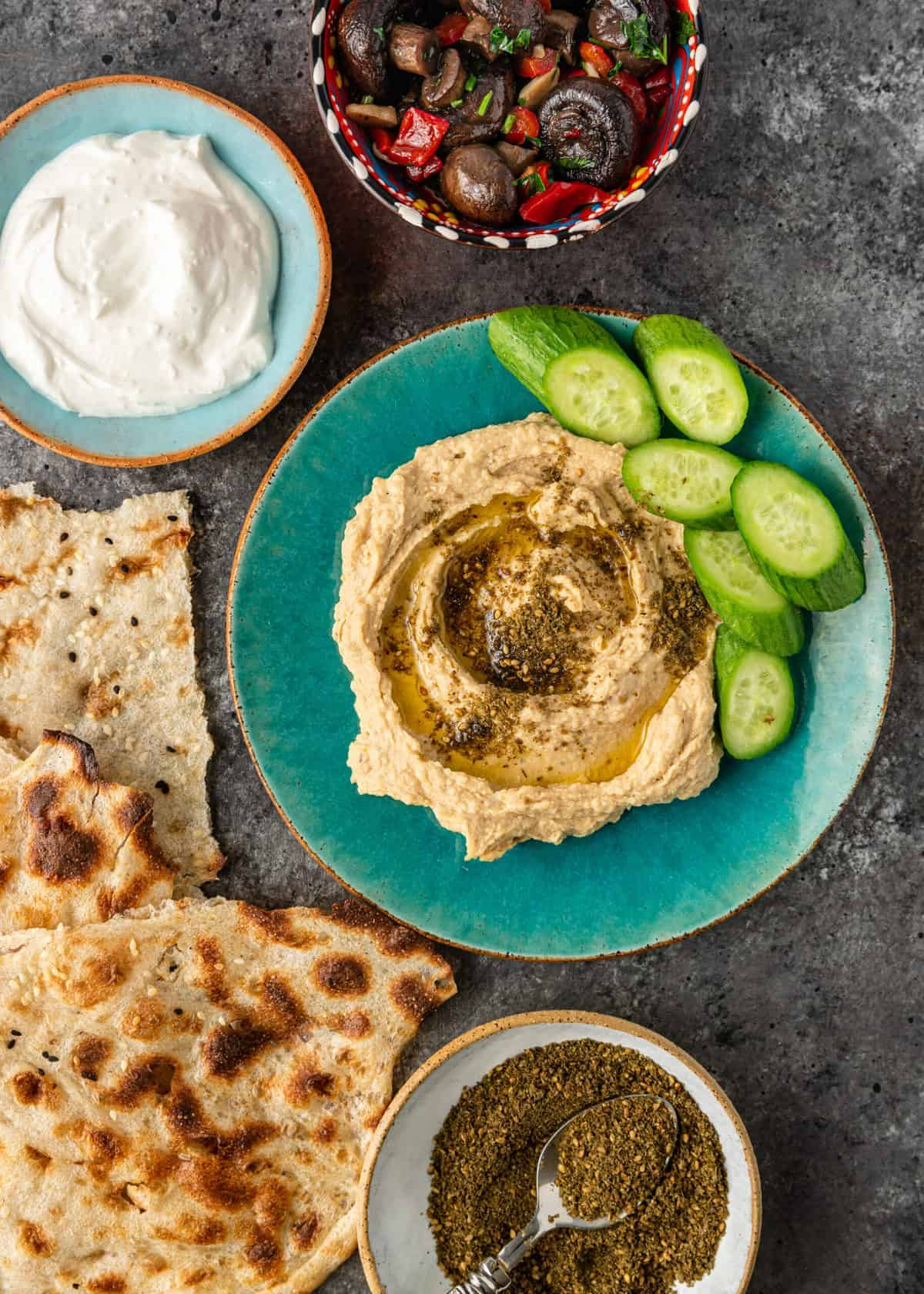 hummus with Lebanese za'tar spice blend on top and sliced cucumbers for dipping