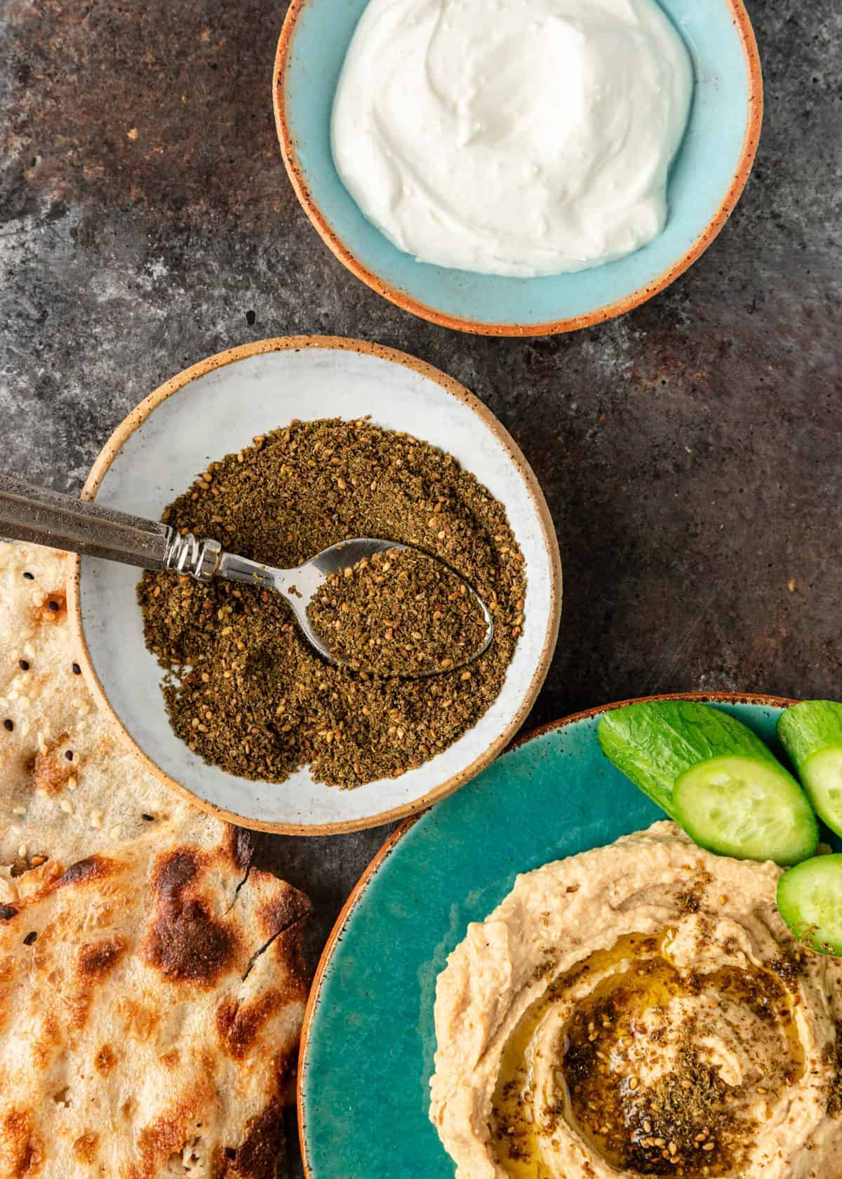 overhead close up of zaatar in bowl with lavash bread hummus and labneh
