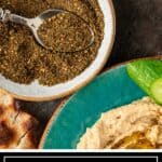 spoonful of zaatar with blue plate of hummus