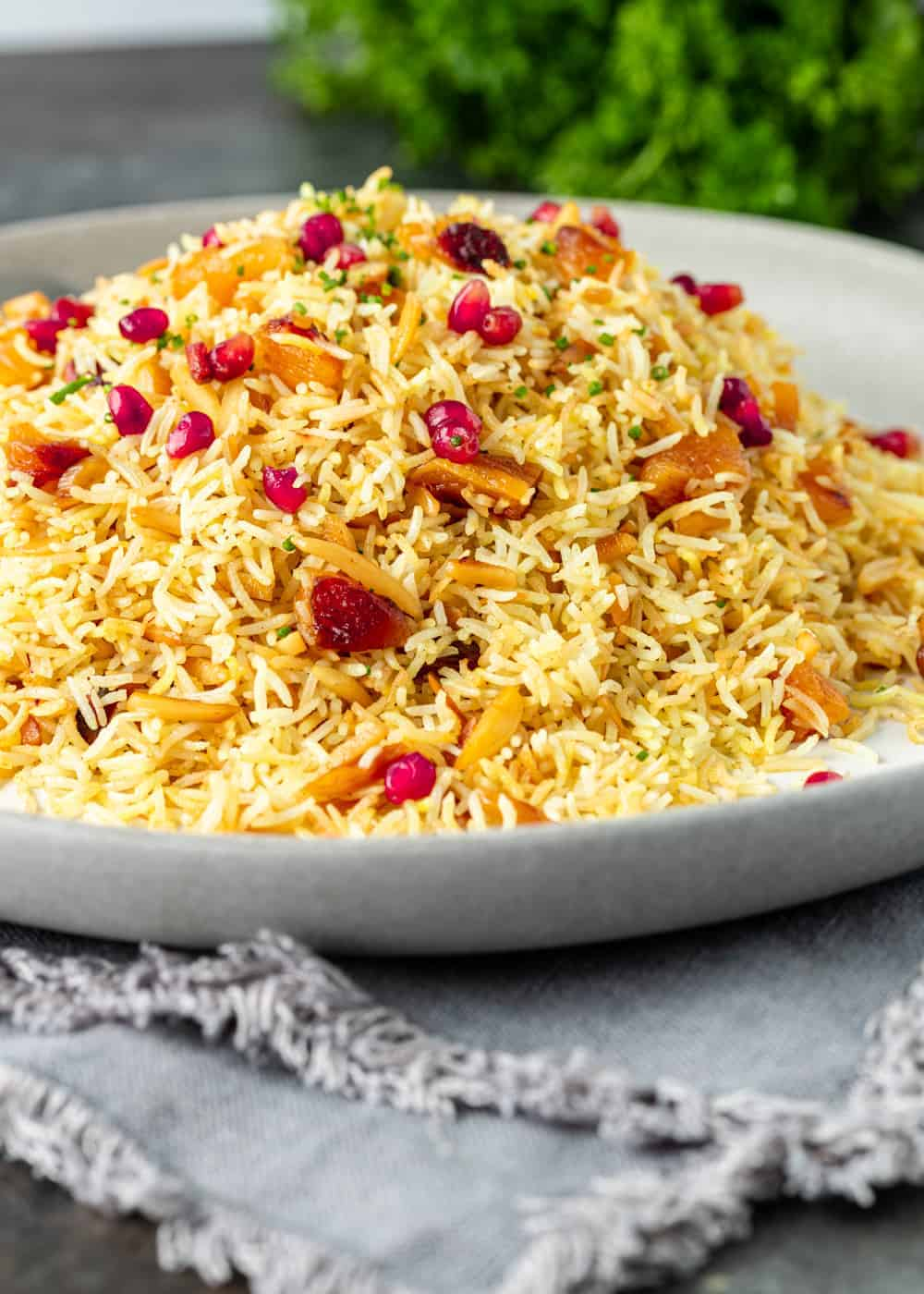 plate of fluffy yellow rice with apricots and pomegranate seeds