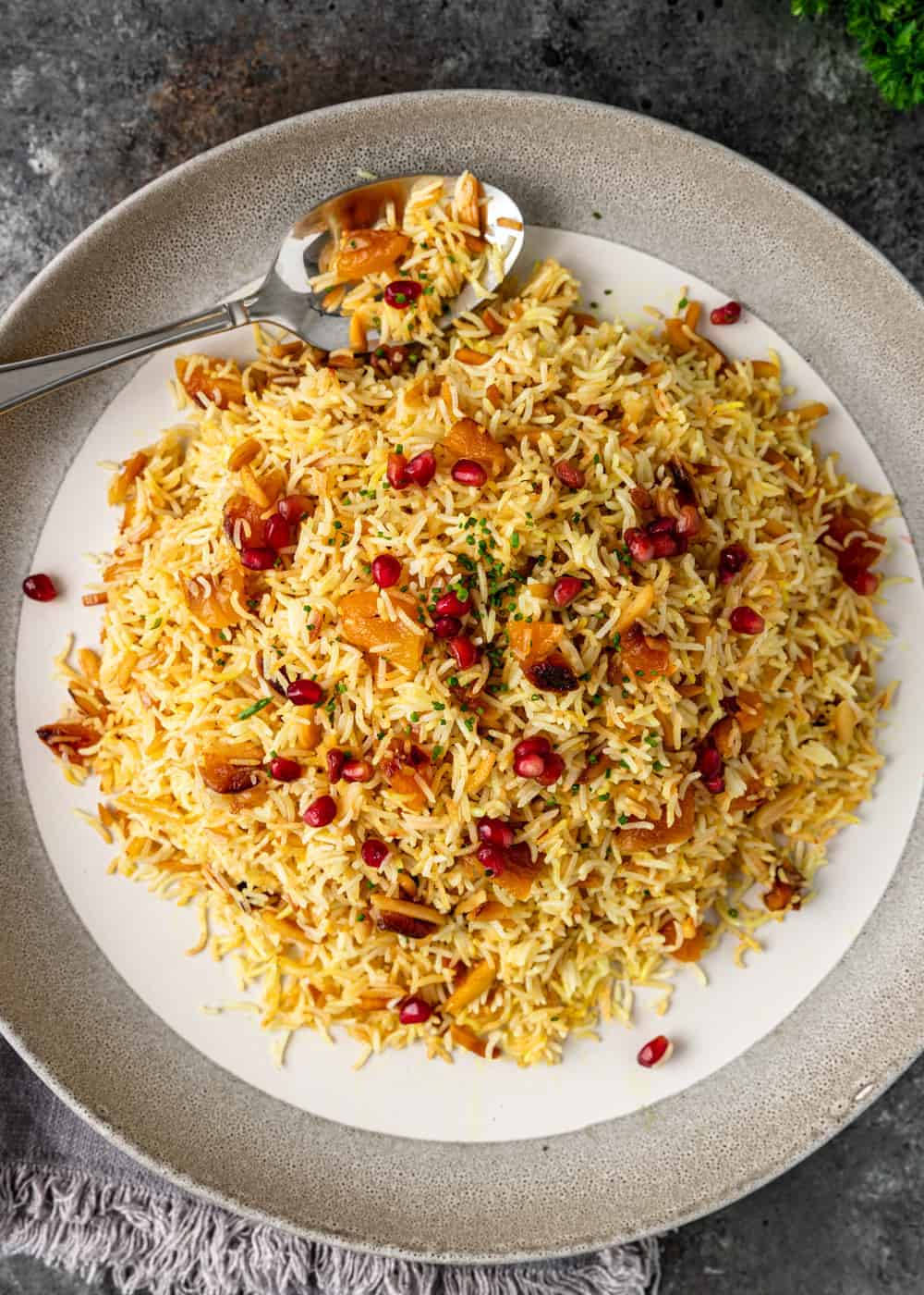 plate of Iranian yellow rice with apricots and pomegranate seeds