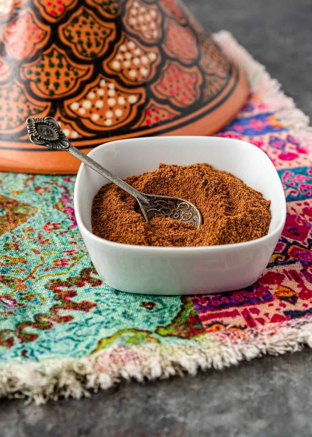 homemade Middle Eastern spices in white bowl with spoon for serving
