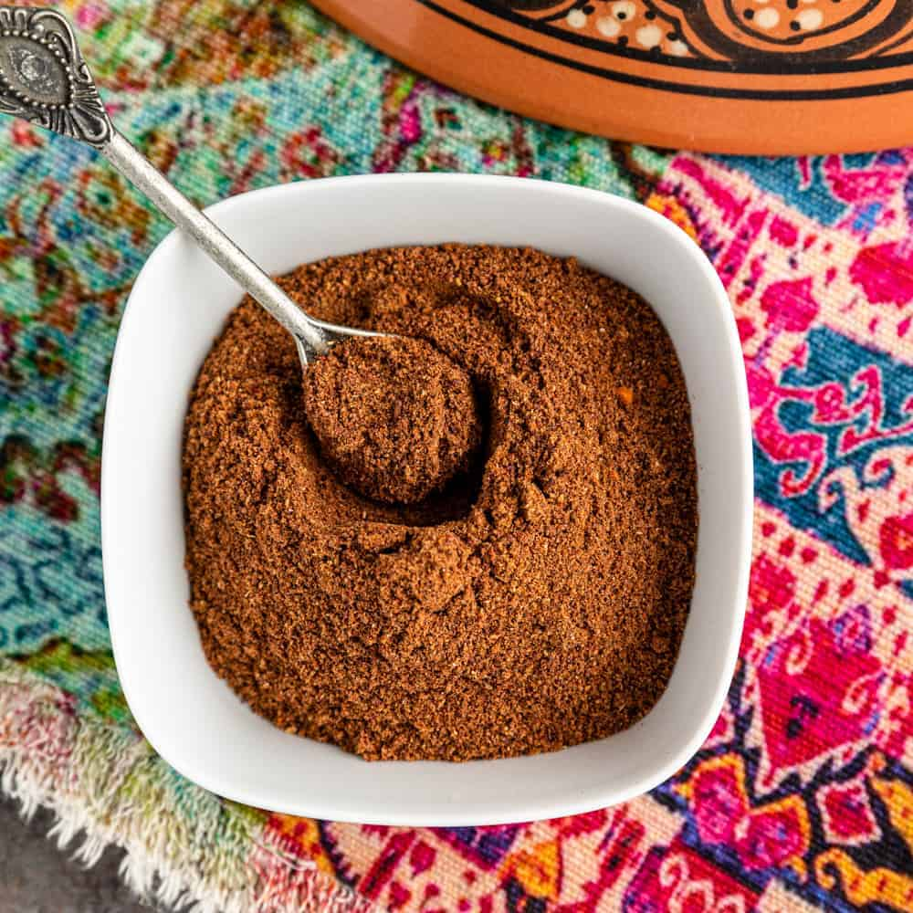 overhead photo: baharat spice blend in white bowl with small serving spoon