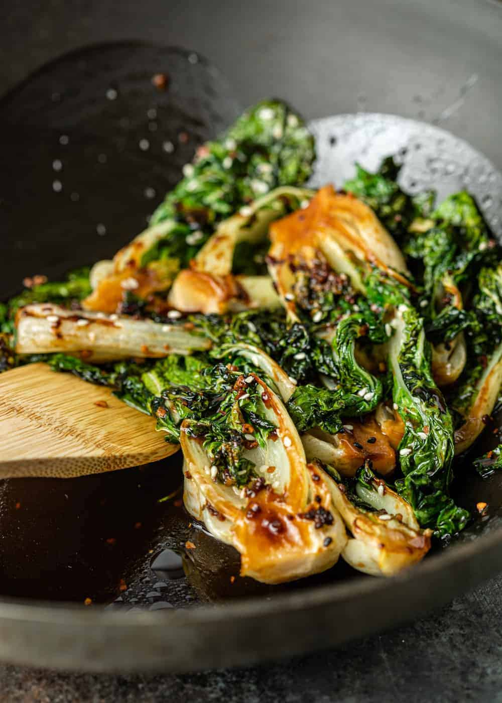 close up photo: sauteed bok choy cabbage and white sesame seeds on wooden spoon