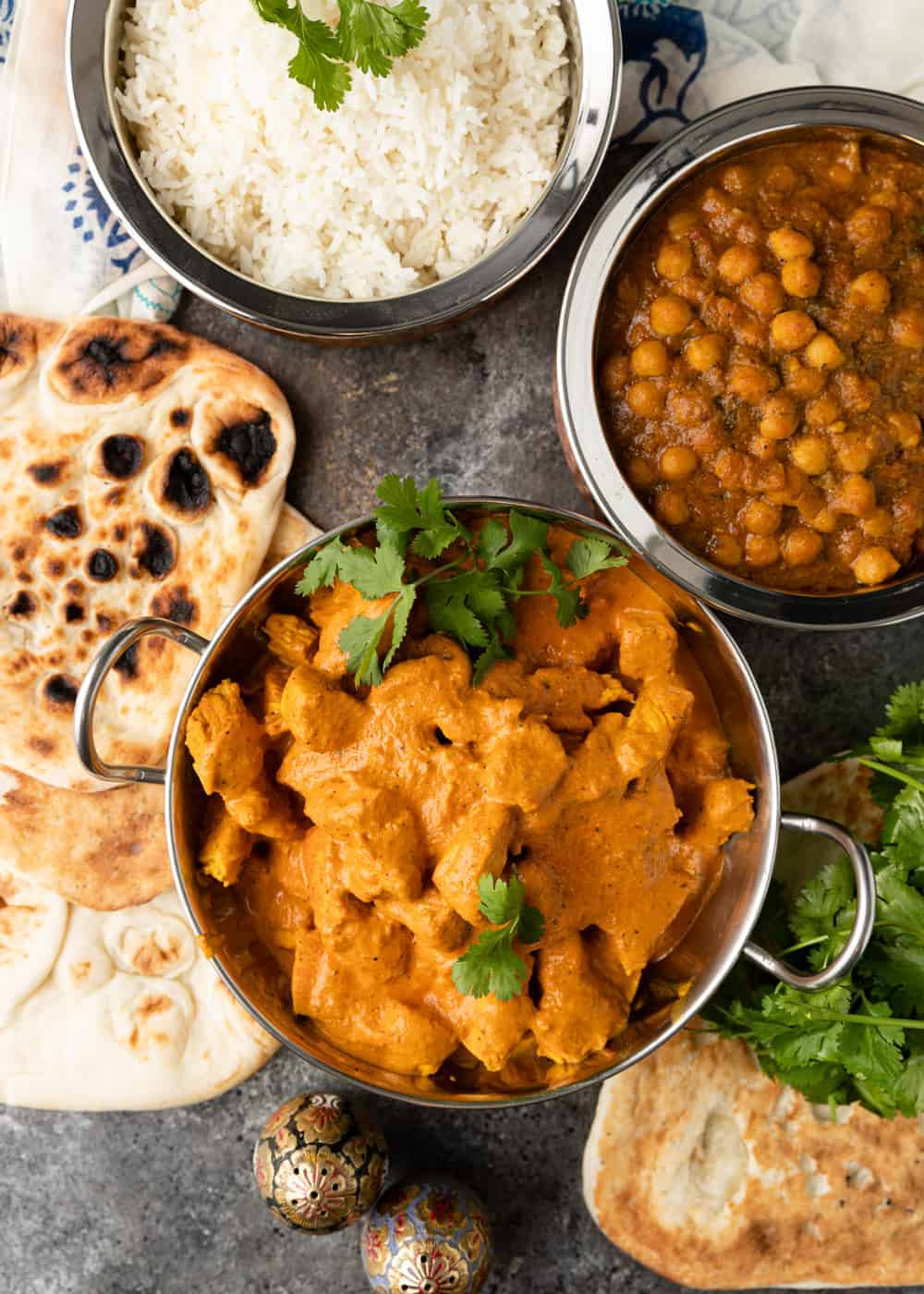 overhead of butter chicken, naan, rice and chickpea curry in copper bowls