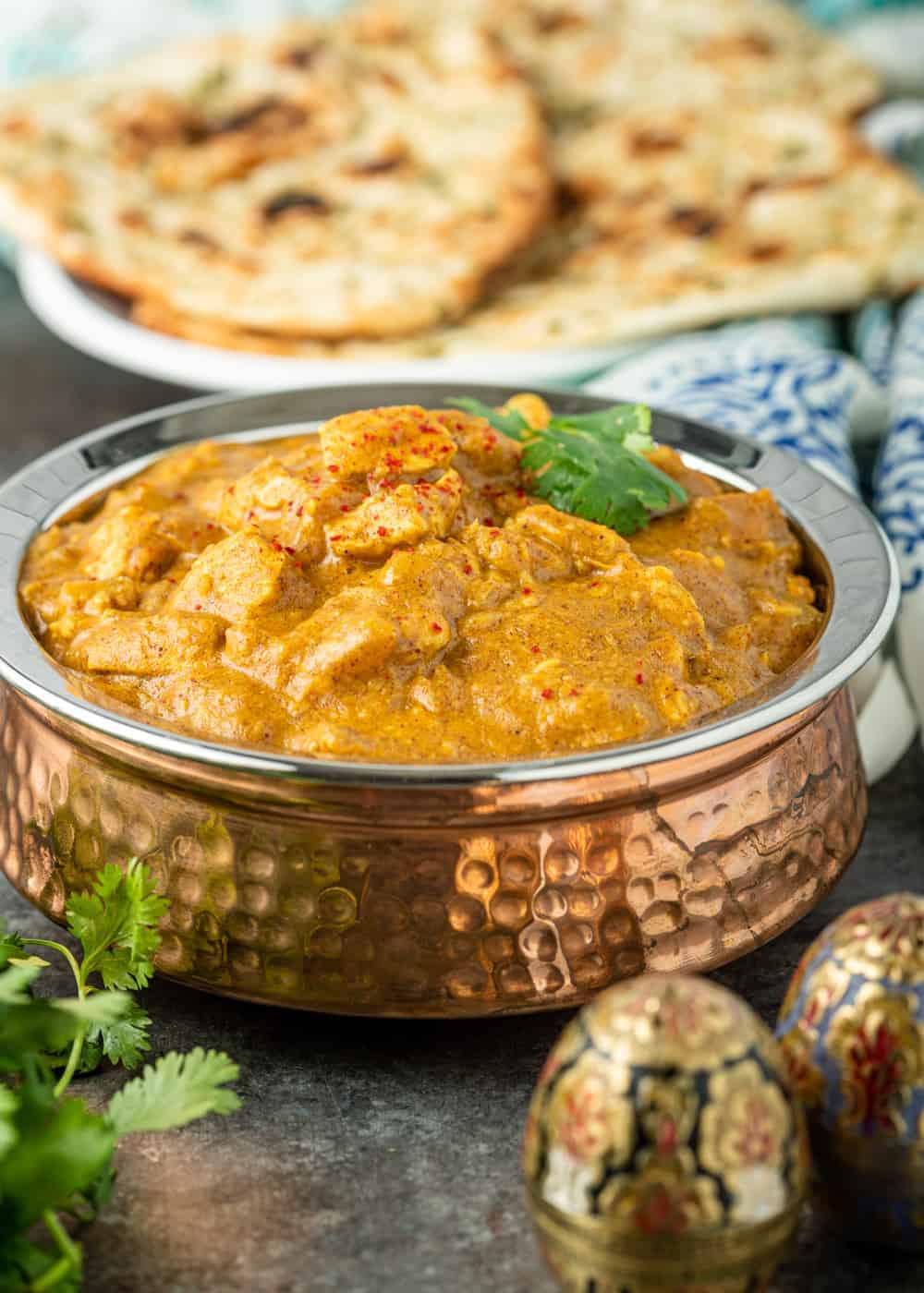 copper serving bowl filled with Indian chicken curry in a creamy sauce