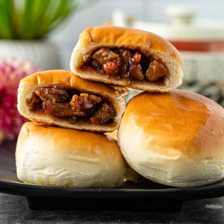 Chinese BBQ pork buns cut open and stacked on top of each other on plate