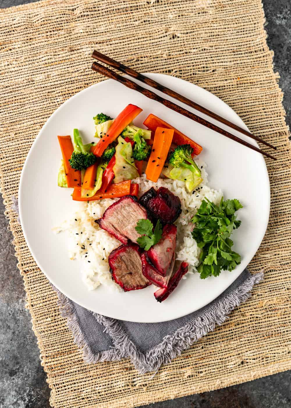 overhead image: plated Asian BBQ pork dinner with side of roasted carrots and broccoli
