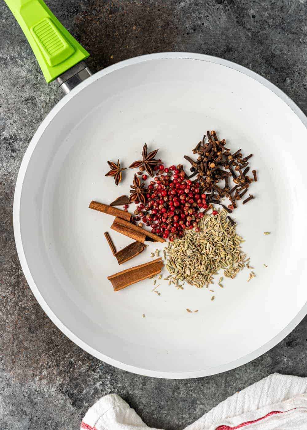 overhead photo of whole spices in skillet for chinese five spice recipe
