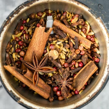 close up of cinnamon sticks, star anise, fennel seeds, cloves, and peppercorns in a spice grinder