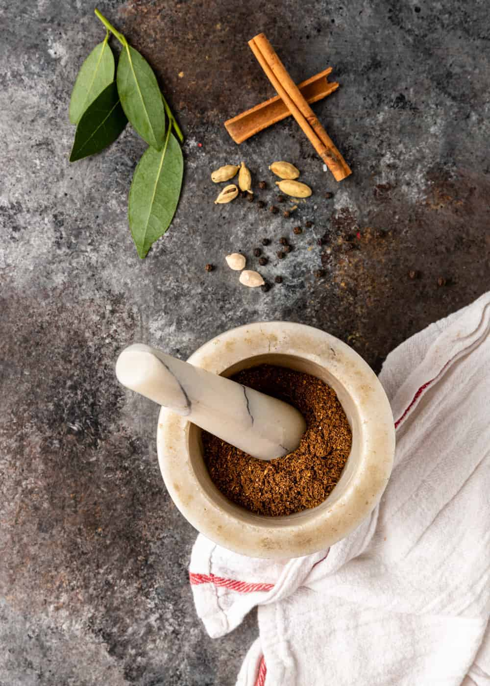 mortar and pestle with garam masala seasoning surrounded by ingredients