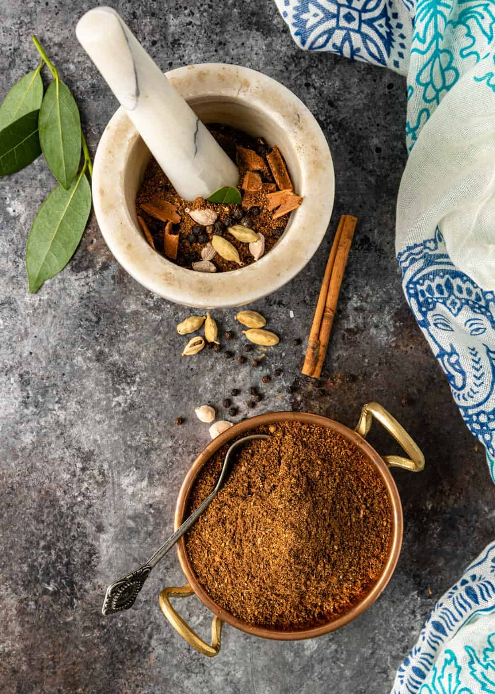 masala seasoning ingredients in a mortar and pestle next to a small bowl with ground spices