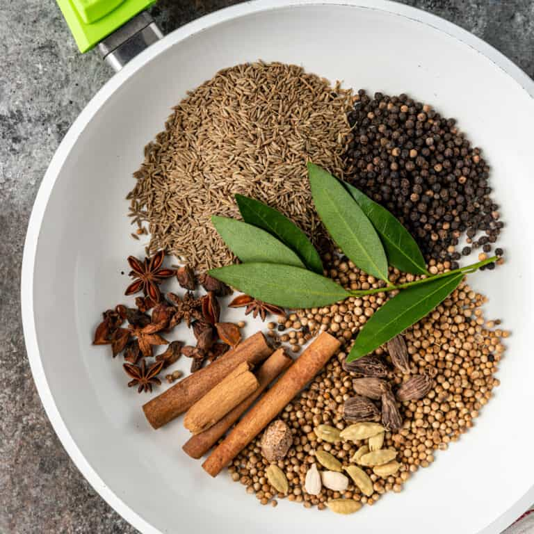 overhead of white skillet with whole spices to make garam masala recipe