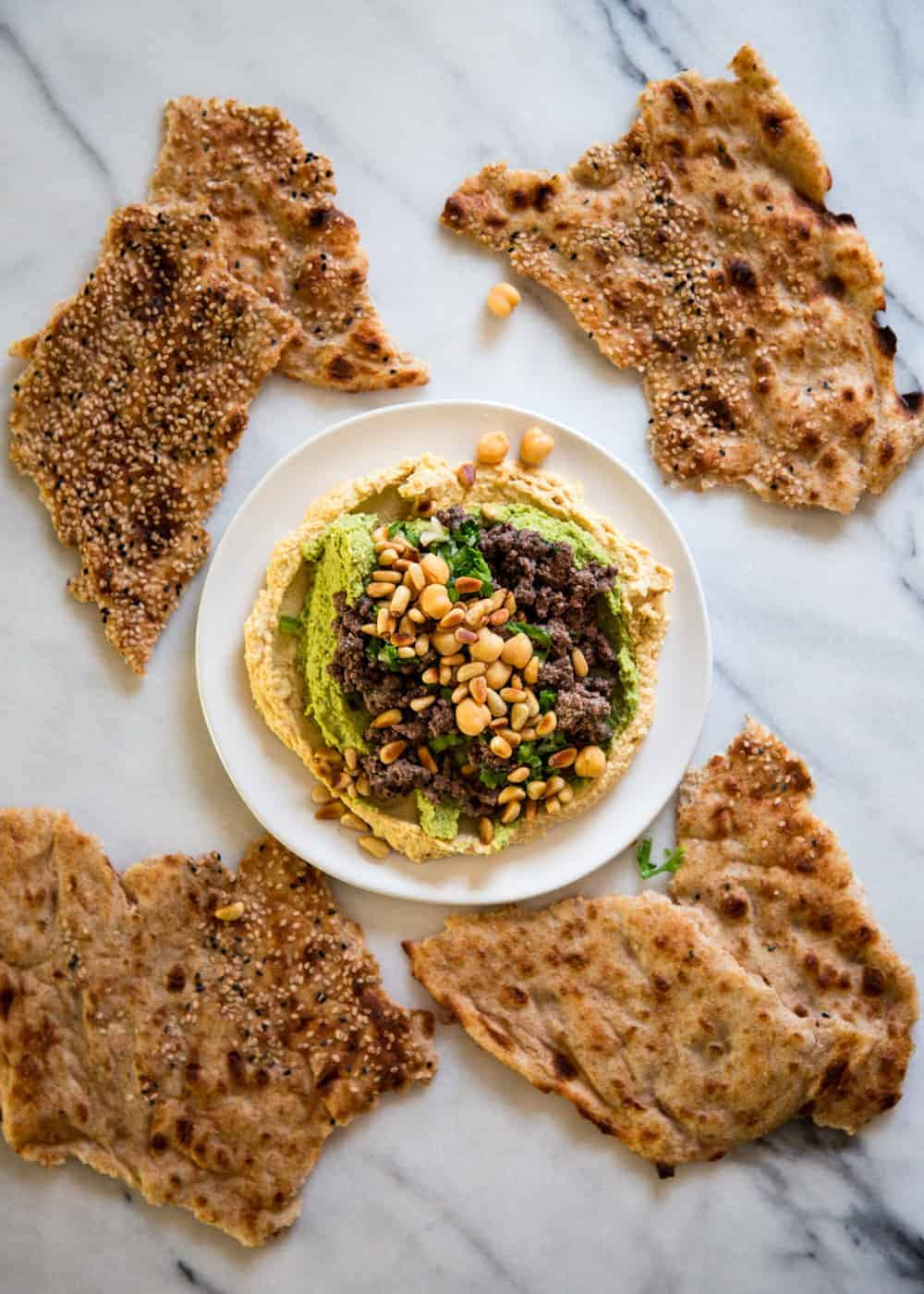 overhead image of hummus kawarma, surrounded by seeded flatbread crackers