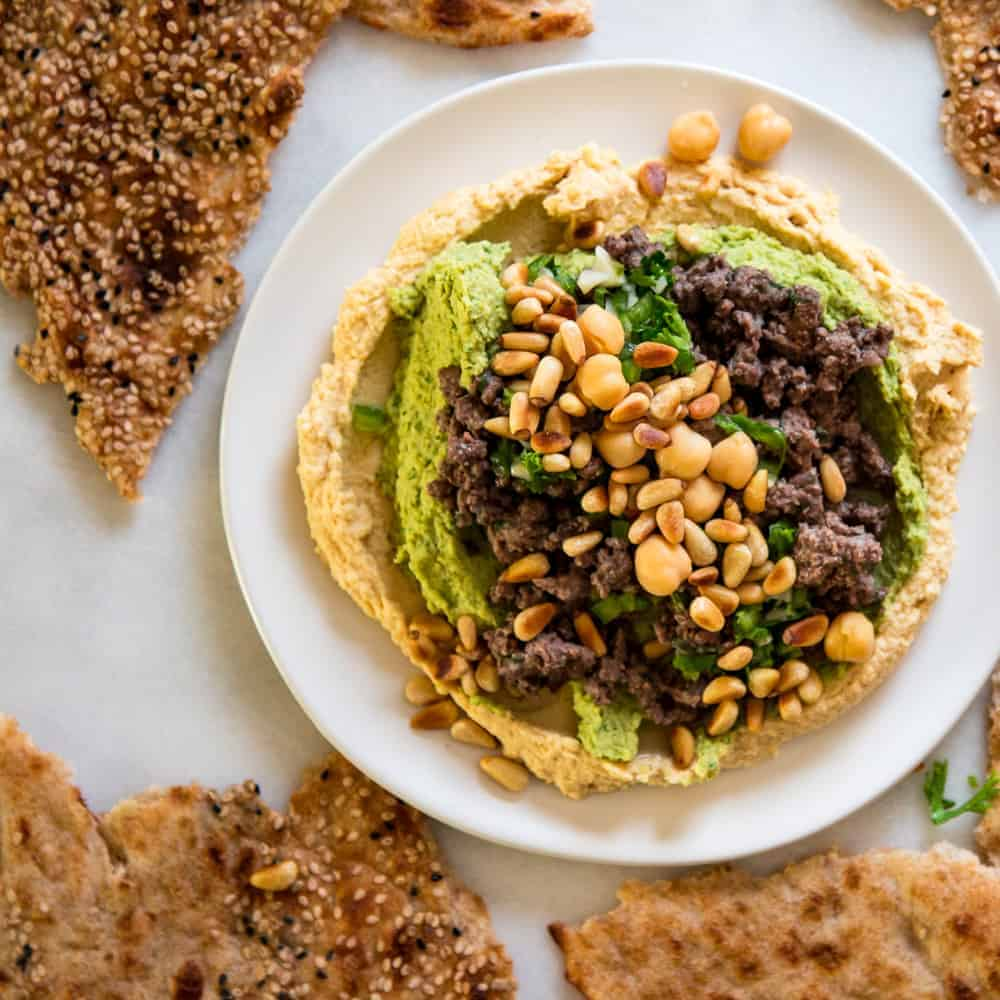 overhead image of lamb hummus on white plate surrounded by flatbread
