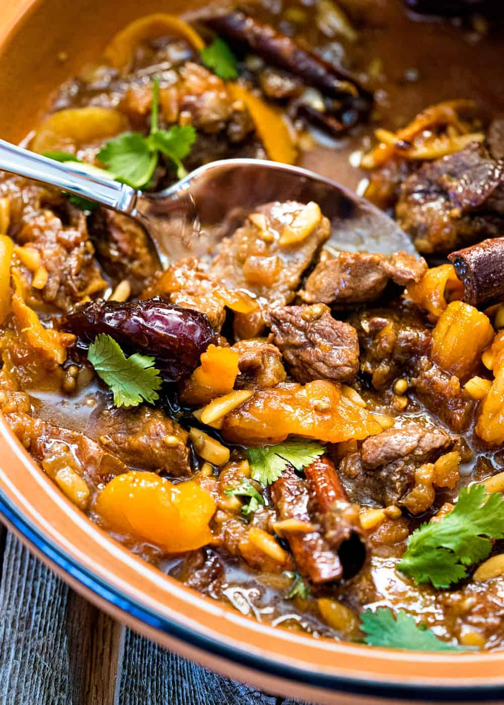 close up image: recipe for lamb tagine in bowl with a spoon