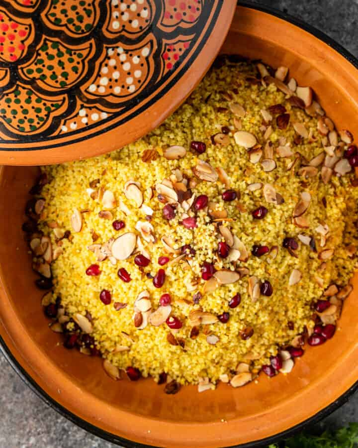 couscous with almonds and pomegranate seeds in a tagine with a decorative lid