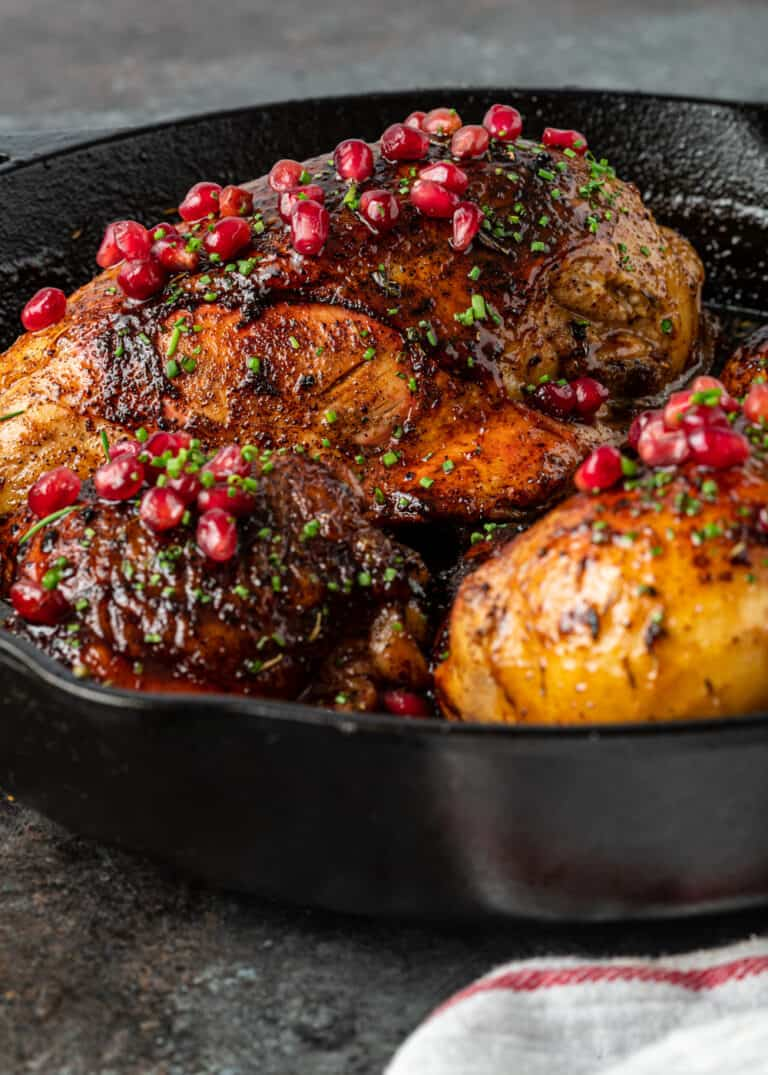 side view: pomegranate chicken in cast iron skillet