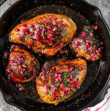 overhead image: 4 pieces of pomegranate molasses chicken in cast iron skillet