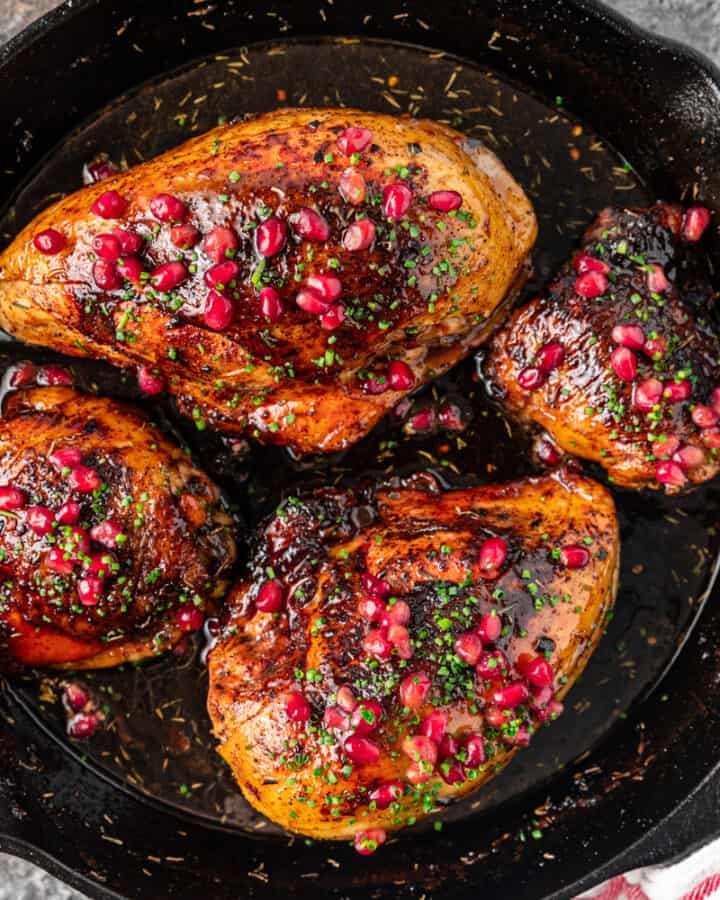 overhead image: 4 pieces of pomegranate chicken in cast iron skillet