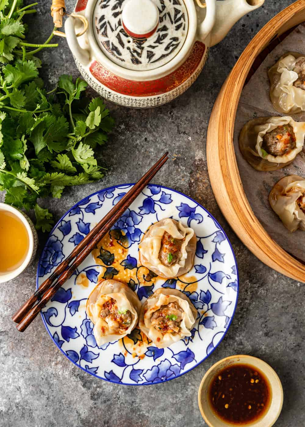 overhead photo of pork shumai on a plate and in a steamer basket with a pot of tea and a bunch of cilantro