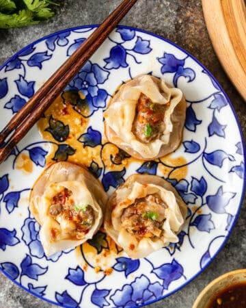 overhead photo of shrimp and pork dumplings on a blue flowered plate with chopsticks