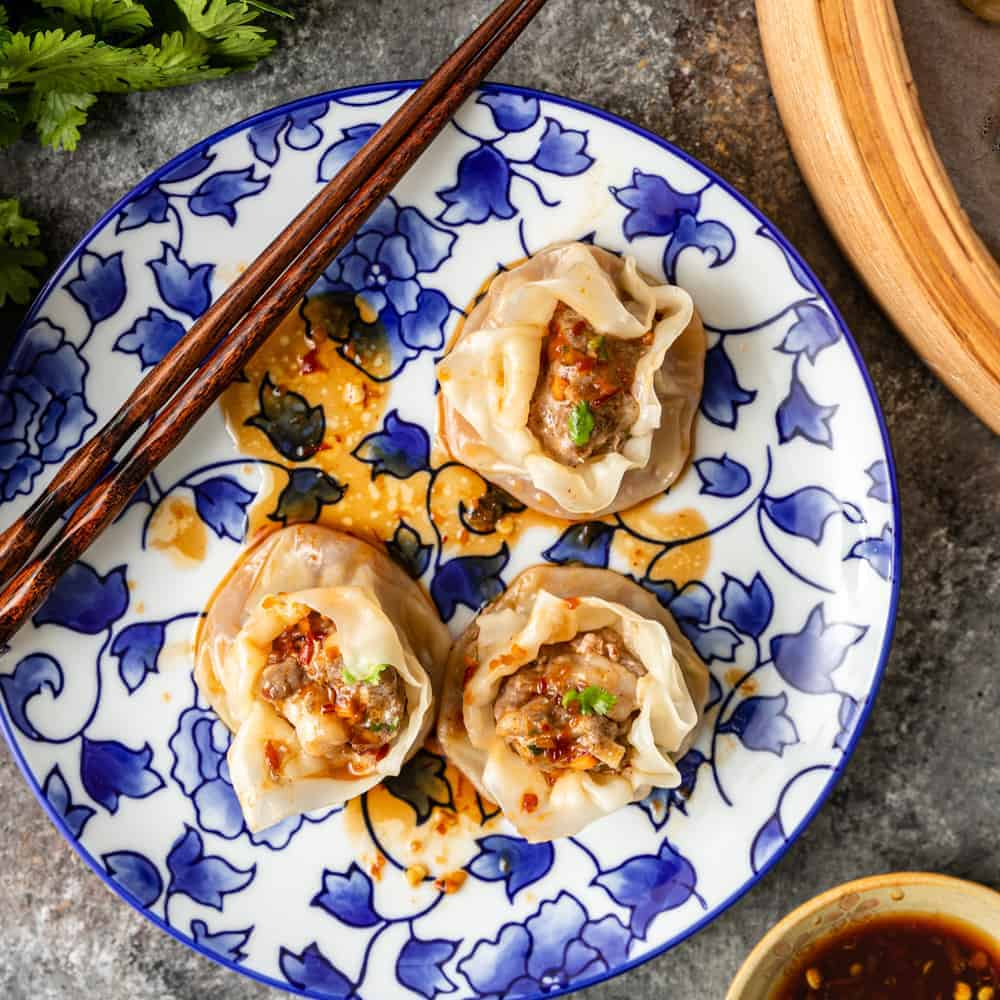 overhead photo of shrimp and pork dumplings on a blue flowered plate with chopsticks