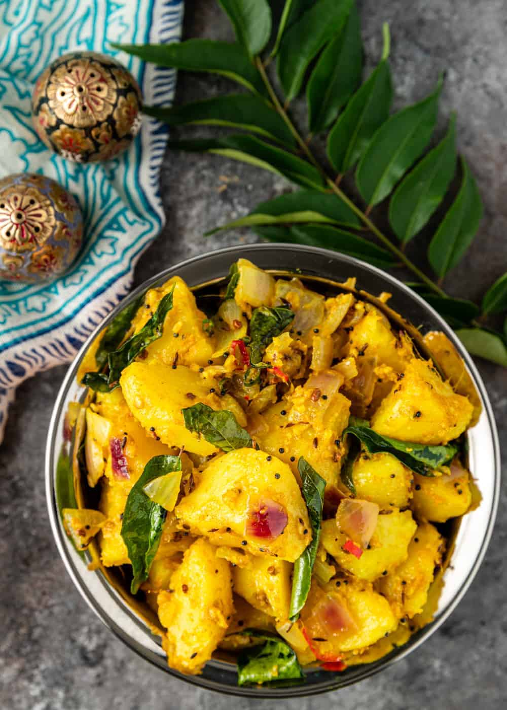 overhead image: dish of cooked potatoes with fresh herbs and Indian spices