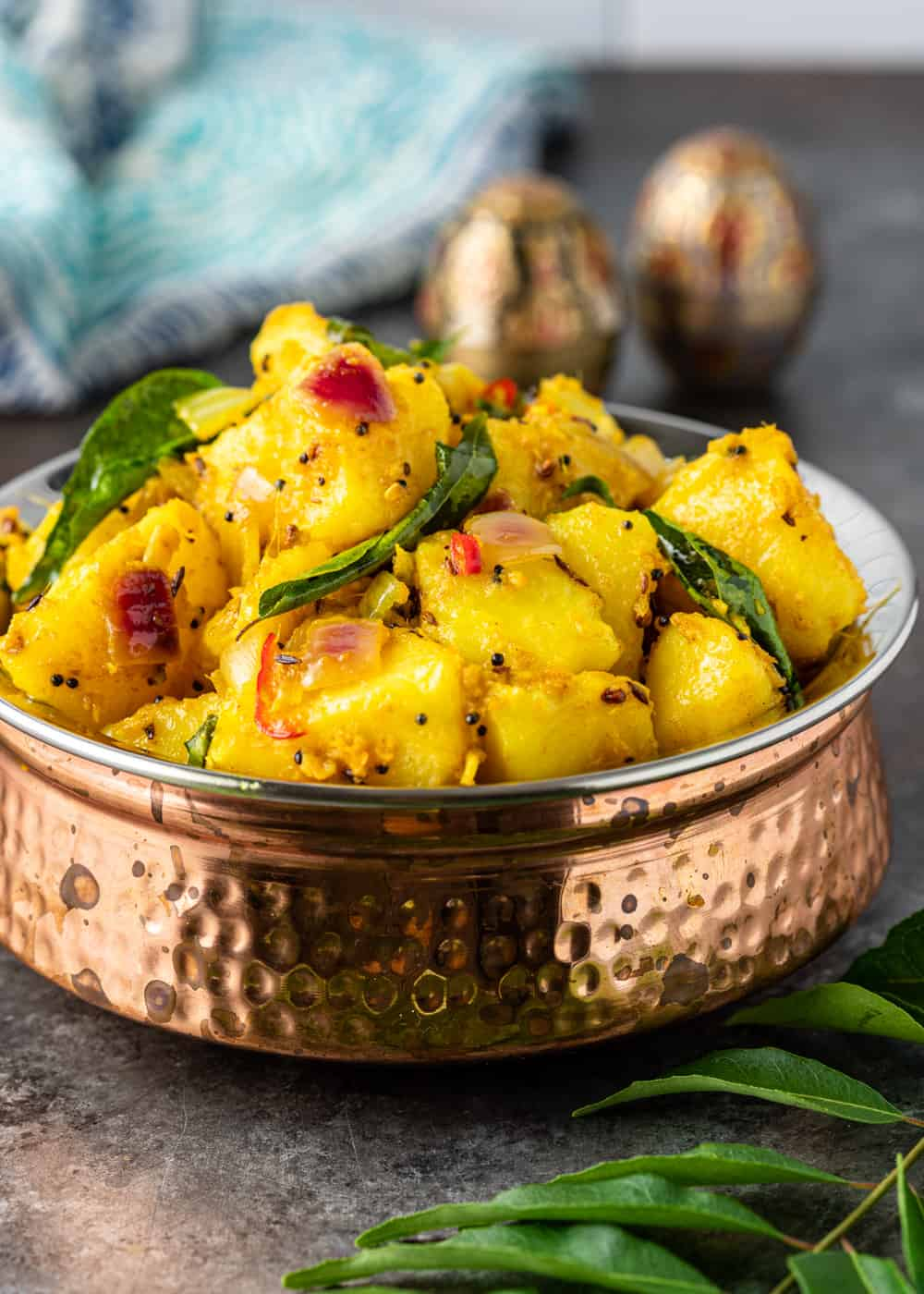 side view: bowl of Indian potatoes side dish known as allo masala