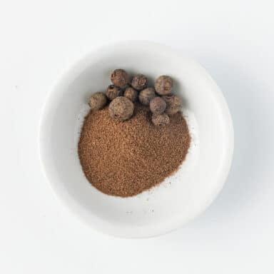 ground allspice with allspice berries in small whit ebowl