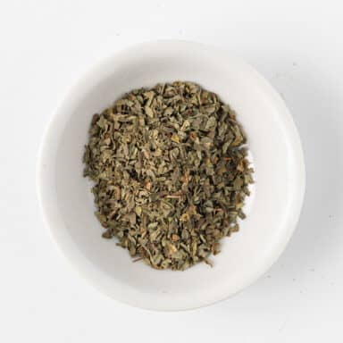 dried basil leaves in small white bowl